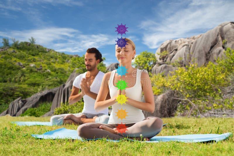Koppla ihop att g?ra yoga i lotusblomma poserar med sju chakras arkivfoton