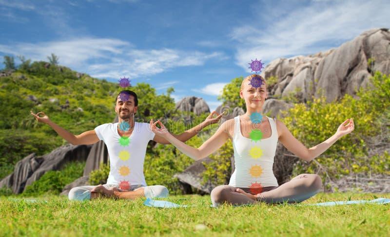 Koppla ihop att g?ra yoga i lotusblomma poserar med sju chakras royaltyfria foton