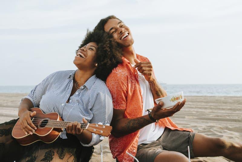 Koppla ihop att ha en picknick på stranden fotografering för bildbyråer