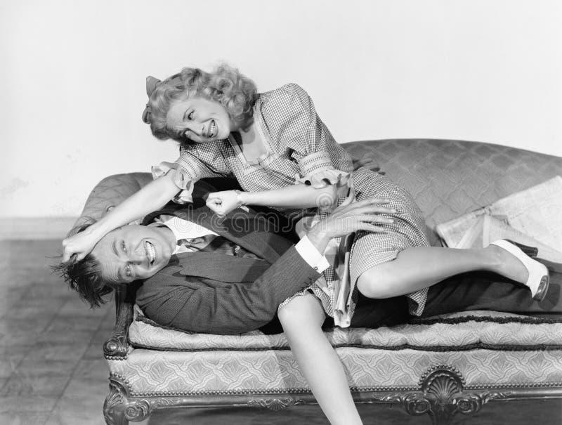 Koppla ihop att ha en skämtsam kamp på en soffa (alla visade personer inte är längre uppehälle, och inget gods finns Leverantörga royaltyfria foton