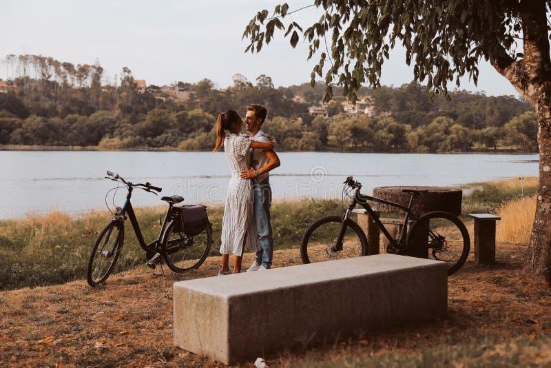 Koppla ihop att ha ett romantiskt datum med cyklar arkivfoton