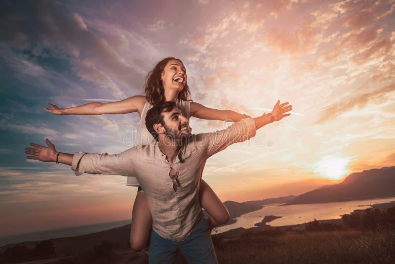 Koppla ihop att ha att ha gyckel i natur, bak dem är en härlig solnedgång över den Boka fjärden arkivfoto