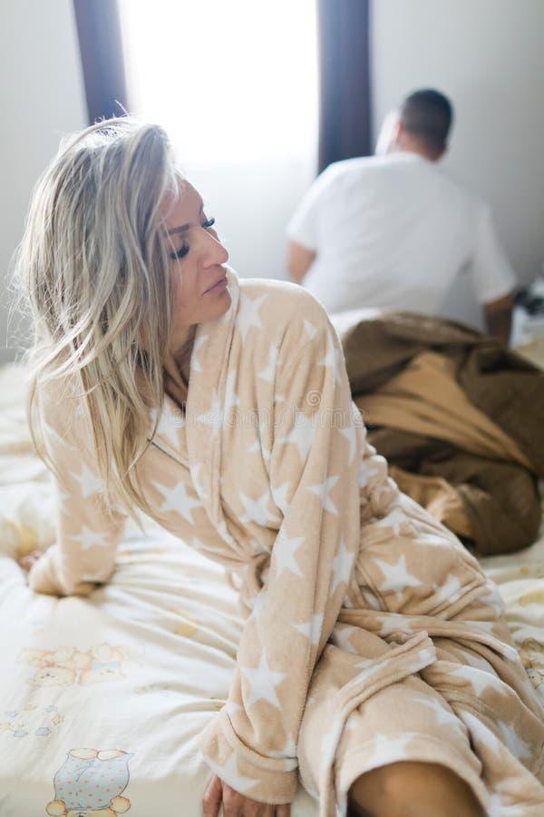 Koppla ihop att ha kris i säng Kvinna som sitter på sängs kant royaltyfri bild