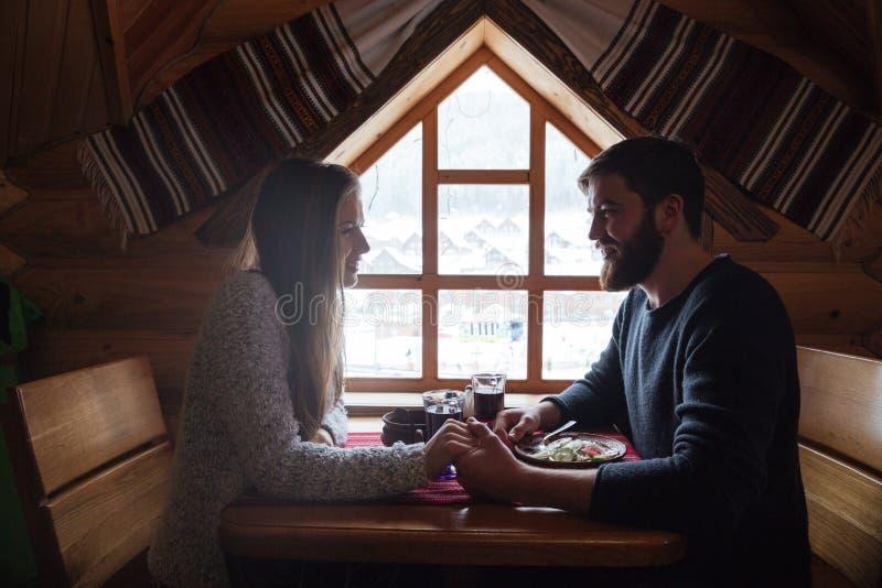 Koppla ihop att ha matställen som sitter tillsammans i trästuga på vinter royaltyfri foto