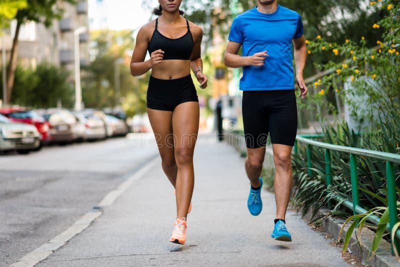 Koppla ihop att jogga på stadsgatan, den kantjusterade framsidan royaltyfria bilder
