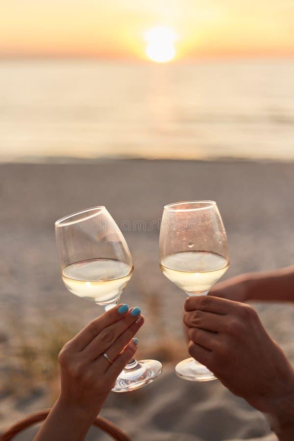 Koppla ihop att klirra exponeringsglas av champagne på solnedgången arkivfoton