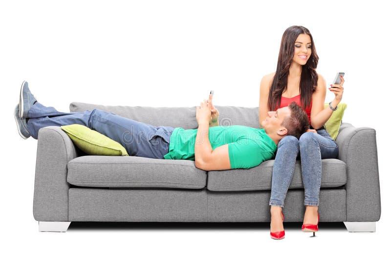 Koppla ihop att koppla av med deras mobiltelefoner på en soffa arkivbild