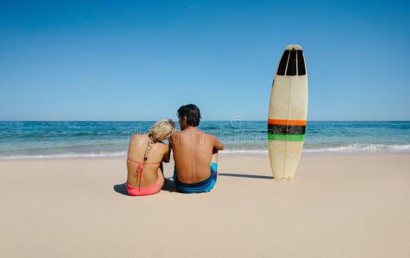 Koppla ihop att koppla av på havskusten med surfingbrädan royaltyfria bilder