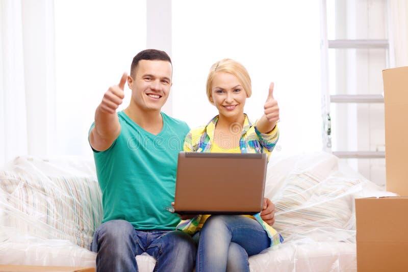 Koppla ihop att koppla av på soffan med bärbara datorn i nytt hem royaltyfria bilder