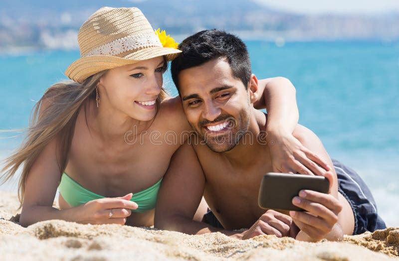 Koppla ihop att koppla av på strand royaltyfria foton