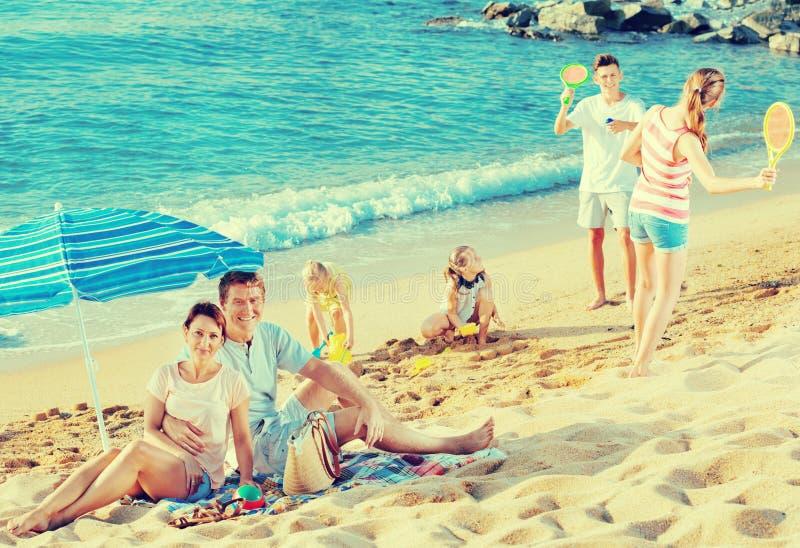 Koppla ihop att koppla av på stranden medan deras ungar som spelar aktiva lekar royaltyfri foto