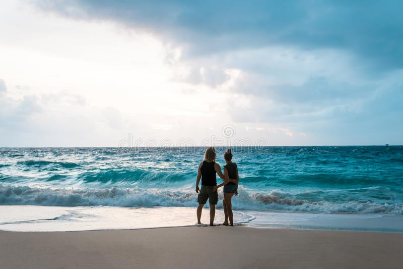 Koppla ihop att krama och att tycka om havsikt på stranden arkivfoton