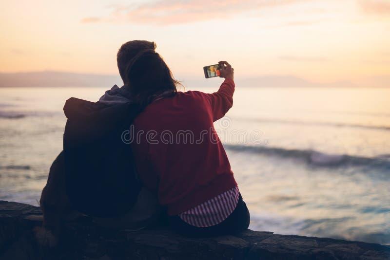 Koppla ihop att krama på soluppgång för bakgrundsstrandhavet, ta foto på den mobila smartphonen, två romantiska personer som kela royaltyfri fotografi