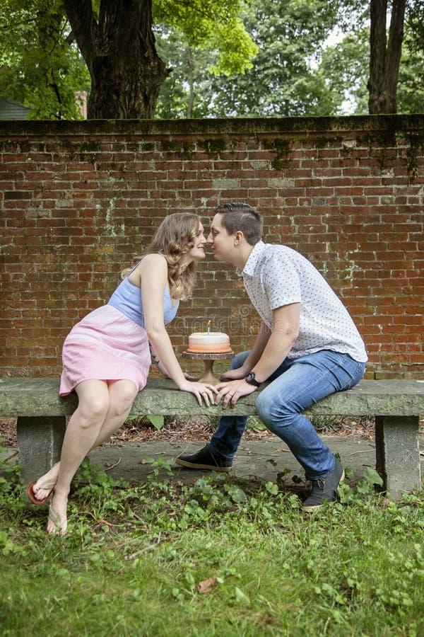Koppla ihop att kyssa över kakan som firar en årsårsdag arkivbilder