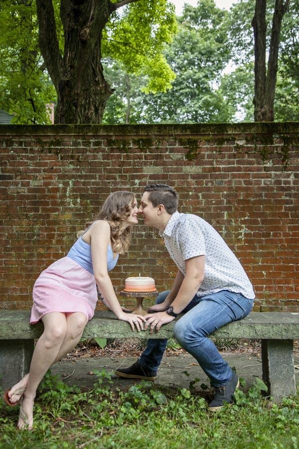 Koppla ihop att kyssa över kakan som firar en årsårsdag royaltyfri foto