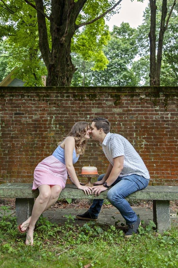 Koppla ihop att kyssa över kakan som firar en årsårsdag royaltyfri bild