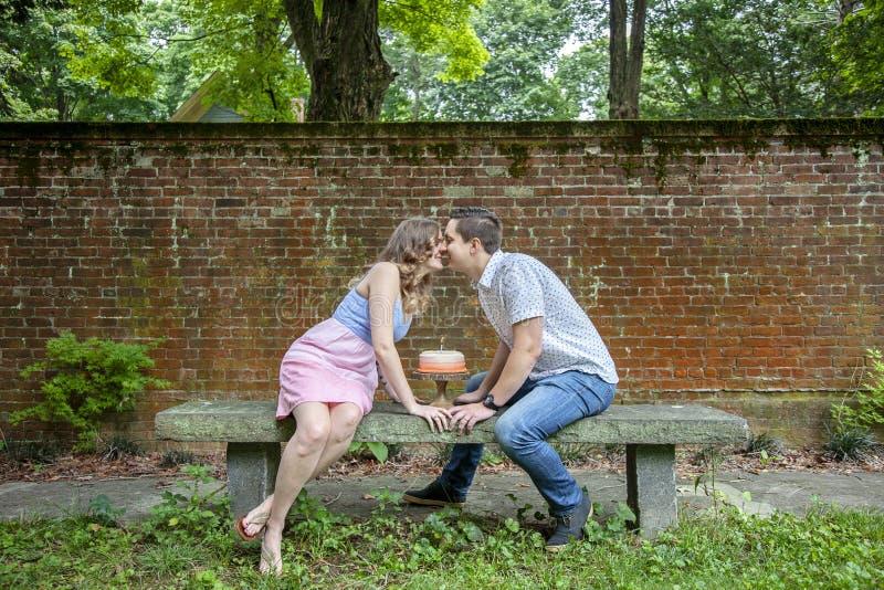 Koppla ihop att kyssa över kakan som firar en årsårsdag royaltyfria bilder