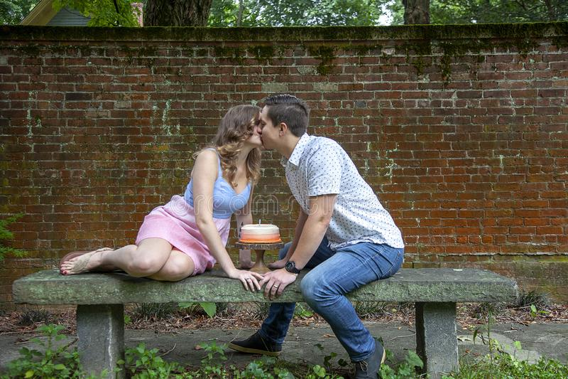 Koppla ihop att kyssa över kakan som firar en årsårsdag arkivfoton