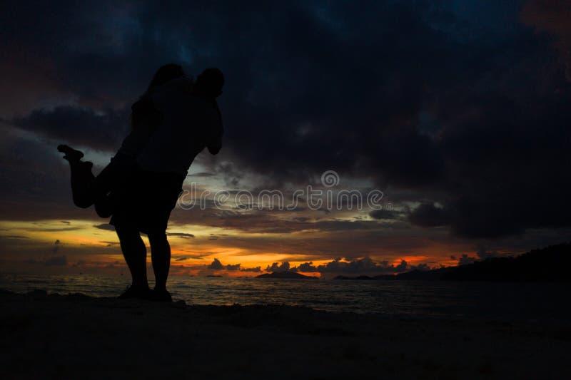 Koppla ihop att kyssa p? stranden med en h?rlig solnedg?ng i bakgrund fotografering för bildbyråer