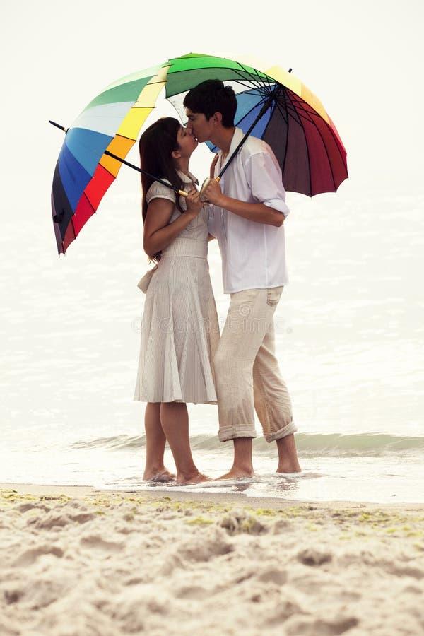 Koppla ihop att kyssa under paraplyet på stranden royaltyfri fotografi