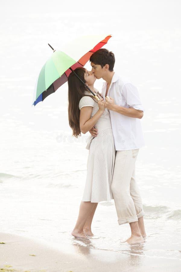 Koppla ihop att kyssa under paraplyet på stranden arkivfoton