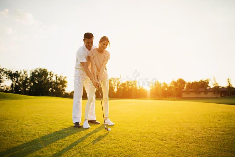 Koppla ihop att lära att spela golf på golfbanan mot solnedgångbakgrunden arkivfoto