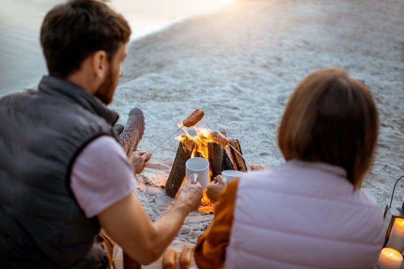 Koppla ihop att laga mat korvar på stranden royaltyfri foto