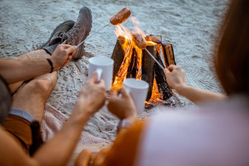 Koppla ihop att laga mat korvar på stranden arkivfoton