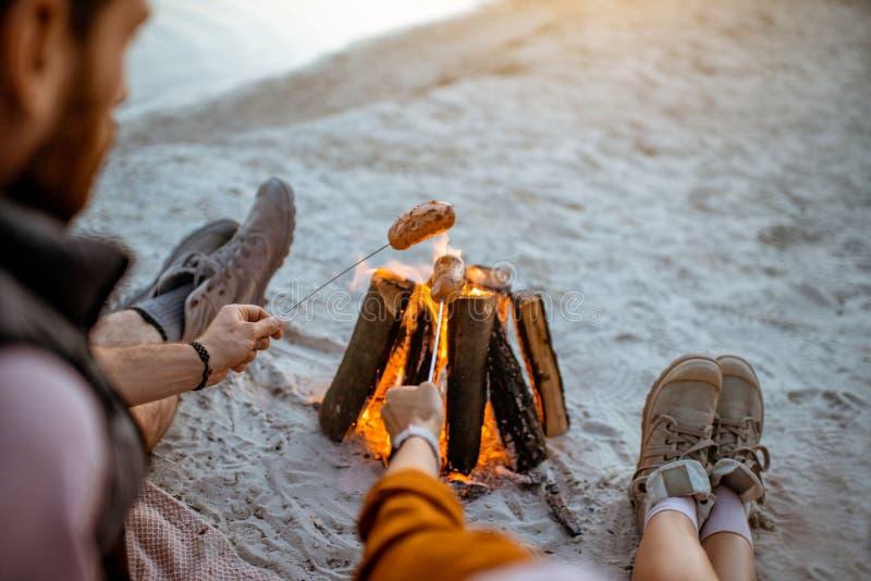 Koppla ihop att laga mat korvar på stranden royaltyfri bild