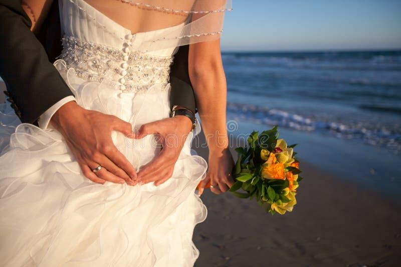 Koppla ihop att le och att omfamna nära bröllopbåge på stranden Bröllopsresa på havet eller havet royaltyfri bild