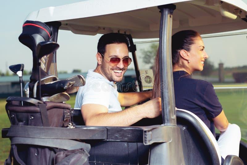 Koppla ihop att le och körning i barnvagn i golfbana arkivfoto