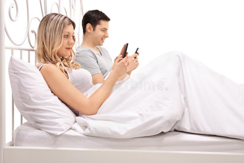 Koppla ihop att ligga i säng och att se deras mobiltelefoner royaltyfri fotografi
