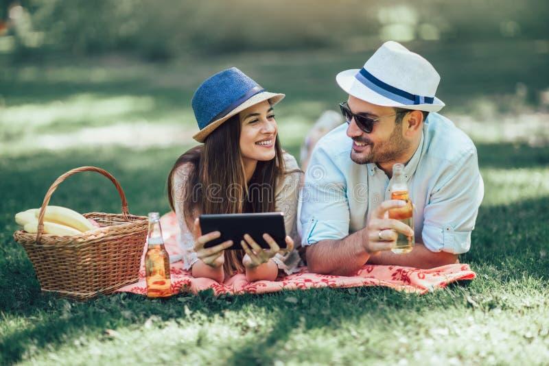 Koppla ihop att ligga på en picknickfilt i en parkera med en picknickkorg som fylls med frukt, dem använder den digitala minnesta arkivfoto