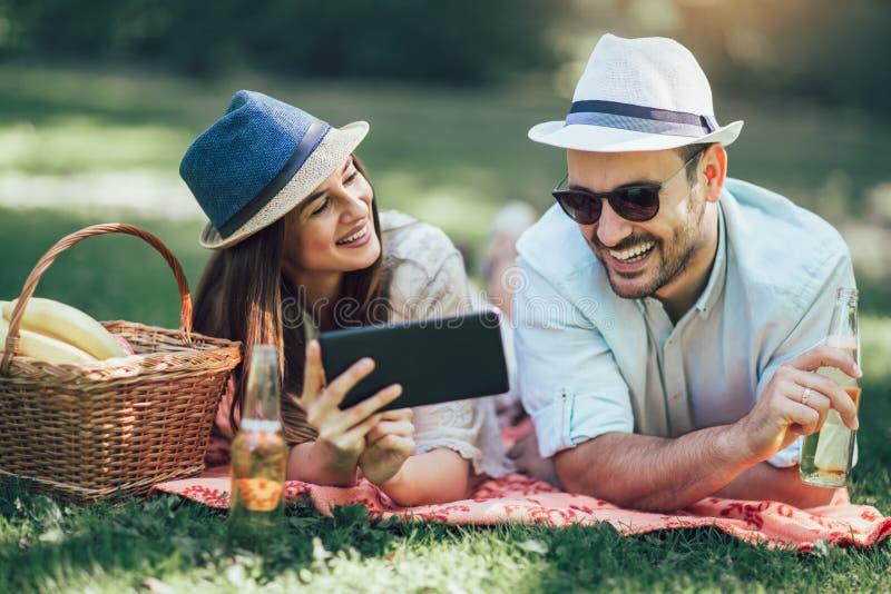 Koppla ihop att ligga på en picknickfilt i en parkera med en picknickkorg som fylls med frukt, dem använder den digitala minnesta arkivfoton