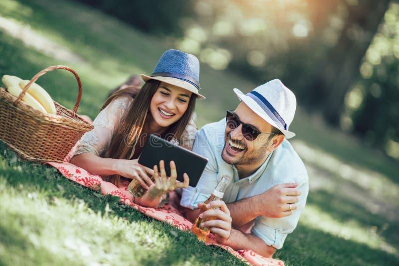 Koppla ihop att ligga på en picknickfilt i en parkera med en picknickkorg som fylls med frukt, dem använder den digitala minnesta arkivbild