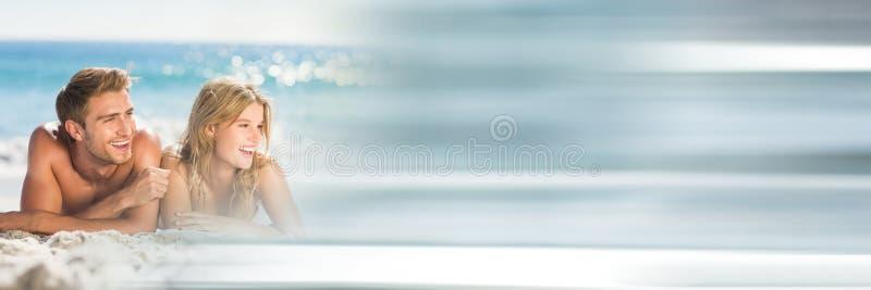 Koppla ihop att ligga på stranden med oskarp grå övergång royaltyfri fotografi