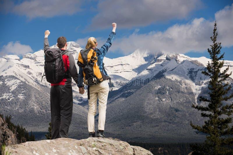 Koppla ihop att lyfta deras händer på överkanten av berg framme av snö-täckte berg royaltyfri bild