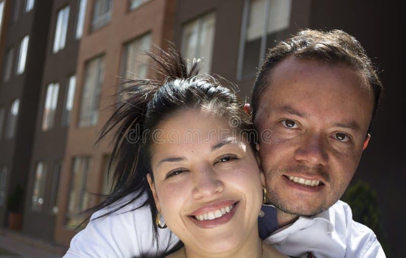 Koppla ihop att omfamna och att le framme av deras nya första hem- arkivfoto