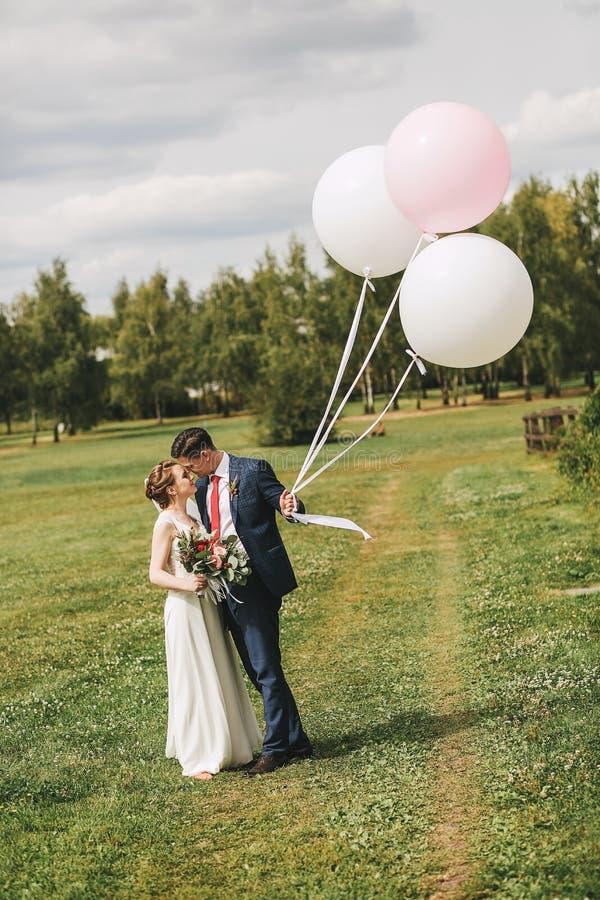 Koppla ihop att omfamna på äng på den soliga dagen med ballonger arkivbild