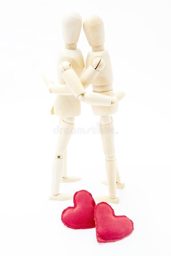 Koppla ihop att omfamna som är förälskat med två hjärtor på din fot royaltyfri bild