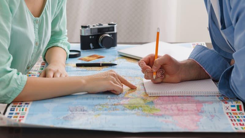 Koppla ihop att planera bröllopsresasemestern som skriver i anteckningsbok royaltyfri bild