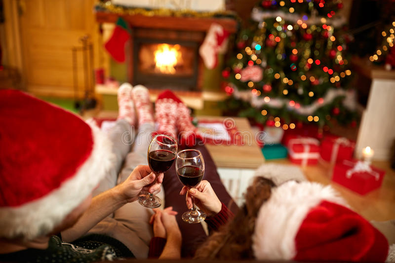 Koppla ihop att rosta med exponeringsglas av rött vin för jul arkivfoton