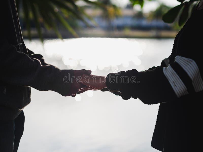 Koppla ihop att rymma händer bredvid den suddiga bakgrunden för sjön Älska & gå tillsammans begreppet arkivbild
