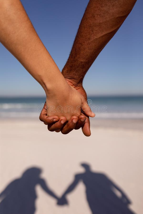 Koppla ihop att rymma händer på stranden i solskenet fotografering för bildbyråer