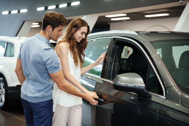 Koppla ihop att söka efter en ny bil på återförsäljarevisningslokalen royaltyfria foton