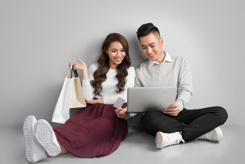 Koppla ihop att shoppa direktanslutet Lyckliga par som ser sittande tillsammans fl arkivfoton