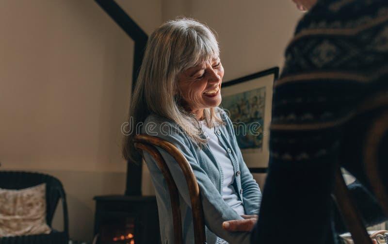 Koppla ihop att sitta hemma samtal till varandra Gammal kvinna som skrattar, medan ha en konversation med en person hemma fotografering för bildbyråer