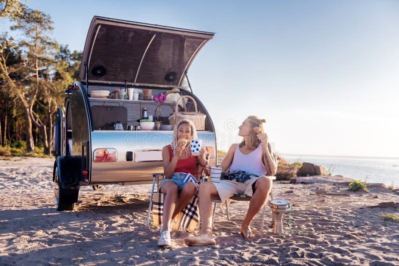 Koppla ihop att sitta på stolar och att äta giffel nära husvagn som används som permanent hem fotografering för bildbyråer
