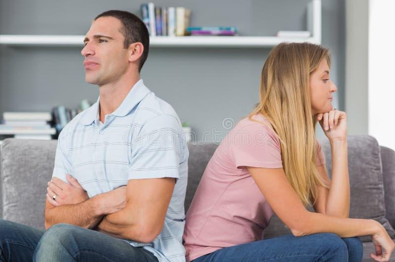Koppla ihop att sitta tillbaka som ska dras tillbaka efter ett slagsmål på soffan royaltyfri foto