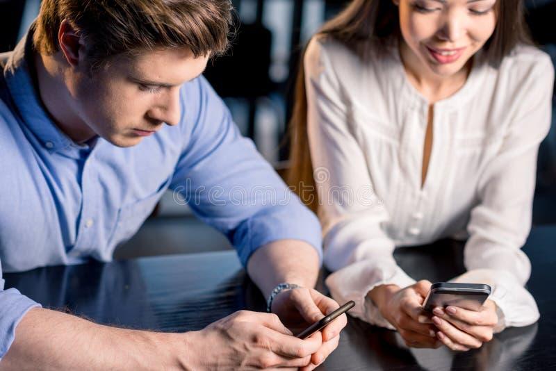Koppla ihop att sitta tillsammans på tabellen och att använda smartphones, begrepp för lunchmöte arkivbild